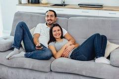 Make och fru som sitter på en soffa arkivbilder