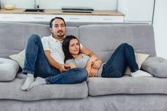 Make och fru som sitter på en soffa arkivbild