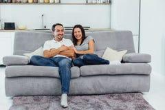 Make och fru som sitter på en soffa royaltyfri fotografi