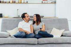 Make och fru som sitter på en soffa arkivfoto
