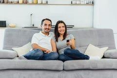 Make och fru som sitter på en soffa royaltyfri foto