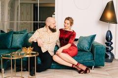 Make och fru som sitter på soffan i ett rymligt ljust rum som tillsammans tycker om varje minut royaltyfri foto