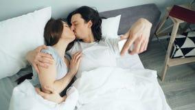 Make och fru som tar selfie med smartphonekameran som kysser att krama i säng stock video