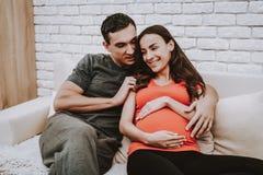 Make och gravid fru som kopplar av på soffan arkivbild