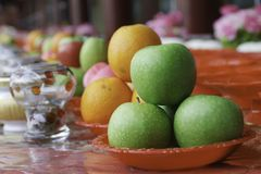 Make offerings or sacrifice to the spirits. Green apple and orange arrangment for religious offerings in china. Make offerings or sacrifice to the spirits Stock Photo