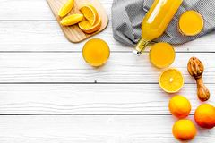 Make orange juice. Juicer, beverage in bottle and glasses near slices of oranges on white wooden background top view Royalty Free Stock Image