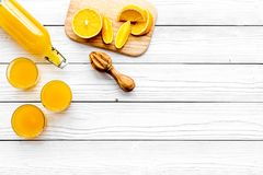 Make orange juice. Juicer, beverage in bottle and glasses near slices of oranges on white wooden background top view Stock Images