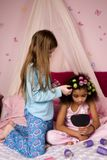 Make-over. Adorable mulatto girl at a slumber party looking in the mirror as her friend puts her hair up in curlers stock image