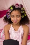 Make-over. Adorable mulatto girl wearing pajamas and colorful curlers and looking into the mirror stock photography