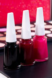 Make over - tree beautiful nail polish colors and make up background - black, dark red and red Stock Photography