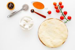 Make pizza concept. Pizza dough and ingredients for filling. Cherry tomatoes, olive oil, cheese mozzarella, spices near royalty free stock image