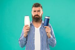 Make right choice. Man bearded hipster choose shampoo or shower gel. Hair care and skin treatment. Choose beauty product royalty free stock photos