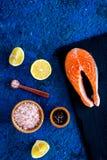 Make salty fish. Raw salmon steak on cutting board near sea salt, pepper, lemon slices on blue background top view copy. Make salty fish. Raw salmon steak on Stock Photography