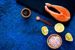 Make salty fish. Raw salmon steak on cutting board near sea salt, pepper, lemon slices on blue background top view copy. Make salty fish. Raw salmon steak on Royalty Free Stock Images
