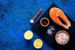 Make salty fish. Raw salmon steak on cutting board near sea salt, pepper, lemon slices on blue background top view copy. Make salty fish. Raw salmon steak on Royalty Free Stock Image