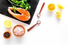 Make salty fish. Raw salmon steak on cutting board near sea salt, pepper, lemon slices on white background top view copy. Make salty fish. Raw salmon steak on Royalty Free Stock Image
