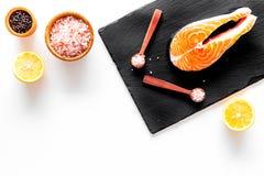 Make salty fish. Raw salmon steak on cutting board near sea salt, pepper, lemon slices on white background top view copy. Make salty fish. Raw salmon steak on Royalty Free Stock Images