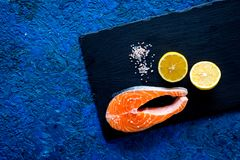Make salty fish. Raw salmon steak on cutting board near slat, lemon slices on blue background top view copy space. Make salty fish. Raw salmon steak on cutting Stock Images