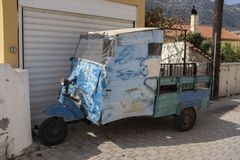 Beat-up old three-wheel truck in back lane in Greece. Make shift, patched up rag tag old three-wheel truck found in the back lane stock photography