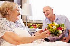 Make som besöker den höga frun i sjukhus med blommor arkivfoton