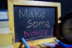 Make some noise! on phrase colorful handwritten on blackboard. Education and business concept. Alarm clock, chalk, books on black background Royalty Free Stock Photography