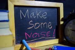 Make some noise! on phrase colorful handwritten on blackboard. Education and business concept. Alarm clock, chalk, books on black background Royalty Free Stock Image