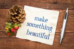 Make something beautiful. Inspirational handwriting on a napkin against rustic wood Stock Image
