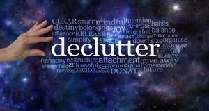 Make space in your life and declutter. Female hand about to pick the word DECLUTTER surrounded by a relevant tag word cloud on a dark deep space night sky Stock Images