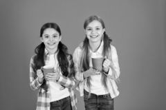 Make sure kids drink enough water. Girls kids hold cups orange background. Sisters hold mugs. Drinking tea while break. Relaxing with drink. Tea break royalty free stock photos