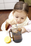 Make a tea. Little girl in flu - maeking a delicious tea with lemon Stock Images