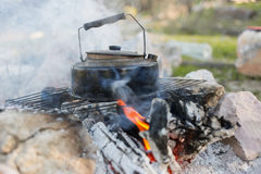 Make tea over an open fire. Royalty Free Stock Photography