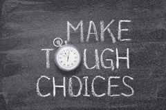 Make tough choices watch. Make tough choices written on chalkboard with vintage precise stopwatch stock photo