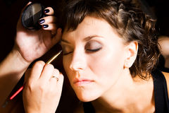 Make-up. Beautician preparing young bride for the wedding and doing make-up Stock Photography