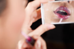 Make-up. Closeup of lady applying lipstick. Selective focus, unrecognizable person Royalty Free Stock Photography