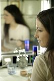 Make up. Auburn-haired girl, young woman putting make up Royalty Free Stock Images