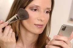 Make up. Blond girl, young woman with pocket looking-glass putting make up Stock Photo