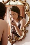 Make up. Auburn-haired girl, young woman putting make up in front of  a mirror Stock Photography