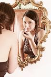 Make up. Auburn-haired girl, young woman putting make up in front of  a mirror Stock Images