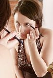 Make up. Auburn-haired girl, young woman putting make up in front of  a mirror Royalty Free Stock Photography