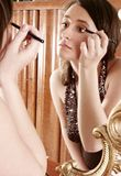 Make up. Auburn-haired girl, young woman putting make up in front of  a mirror Stock Photo