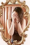 Make up. Auburn-haired girl, young woman in front of  a mirror Stock Image