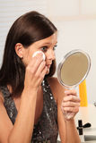 Make up. Brunette woman putting on her make up royalty free stock photography