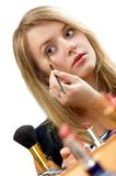 Make-up. Young beautiful woman is making up for itself in front of a mirror Royalty Free Stock Photography