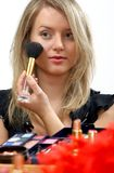 Make-up. Young beautiful woman is making up for itself in front of a mirror Stock Photo