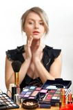 Make-up. Young beautiful woman is making up for itself in front of a mirror Stock Photos