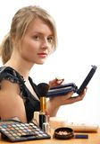 Make-up. Young beautiful woman is making up for itself in front of a mirror Stock Photography