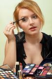 Make-up. Young beautiful woman is making up for itself in front of a mirror Stock Image