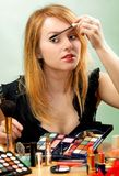 Make-up. Young beautiful woman is making up for itself in front of a mirror Royalty Free Stock Images