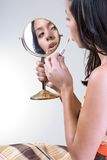 Make-up. Female holds a mirror applying make-up Stock Images