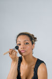 Make up. Pretty mixed race teen putting on make up Royalty Free Stock Photography